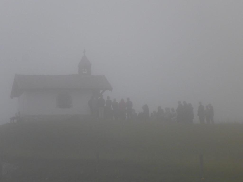 Menschen vor Kapelle im Nebel