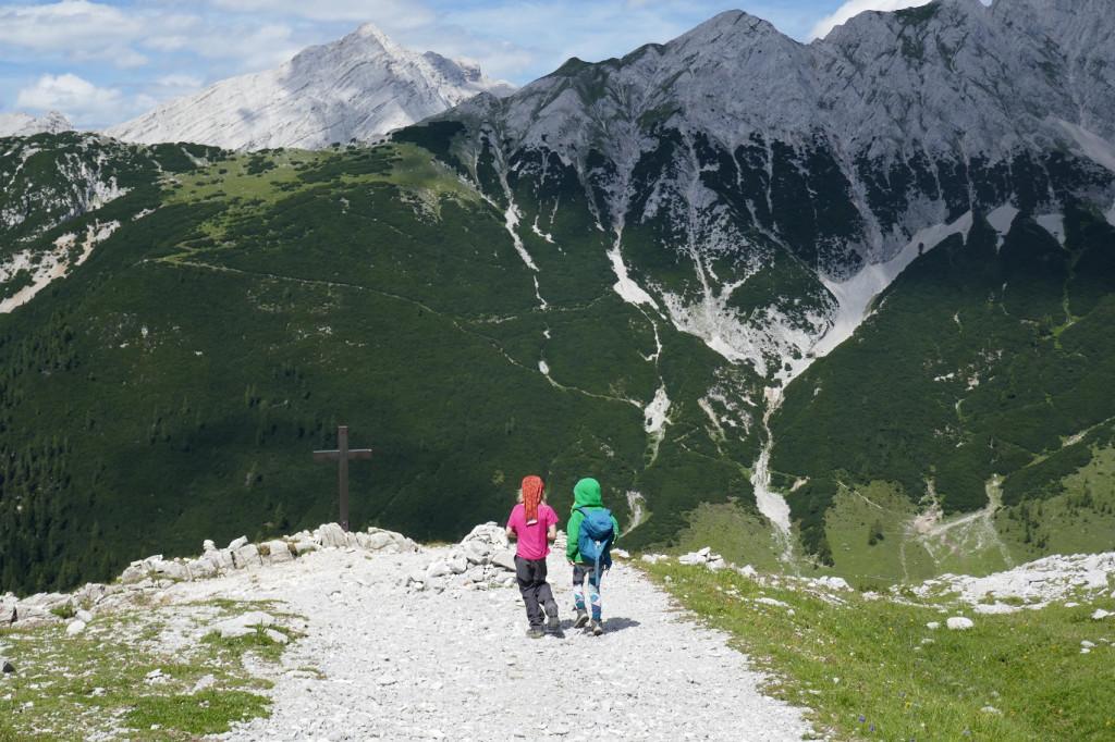 Kinder in den Bergen, mit Kreuz im Hintergrund